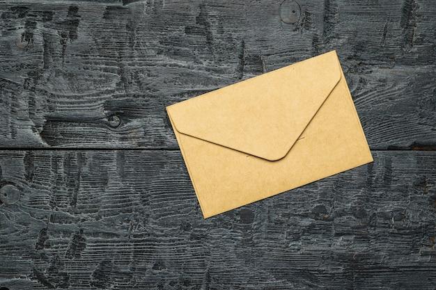 Бумажный почтовый конверт на деревянном столе. понятие почтовой переписки. плоская планировка.