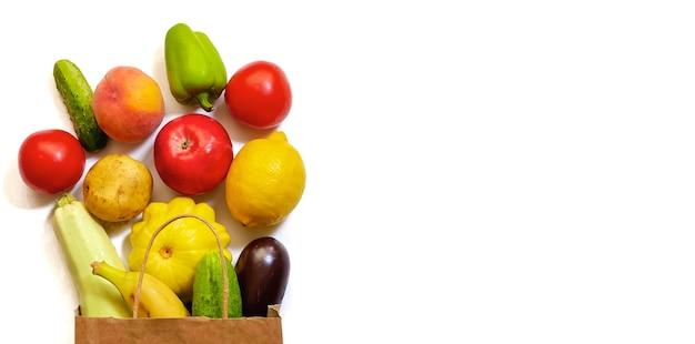 白い背景に野菜や果物、トマト、キュウリ、スカッシュ、コショウ、レモン、ナス、ズッキーニ、バナナ、リンゴ、桃が入った紙の買い物袋。オンラインショッピングのコンセプト。