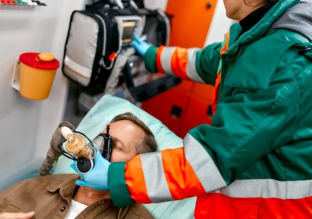 制服を着た救急医療の女性は、現代の救急車の担架にパルスオキシメータを置いて横たわっている高齢の患者を助けるために、酸素を入れた人工呼吸器を装着します。