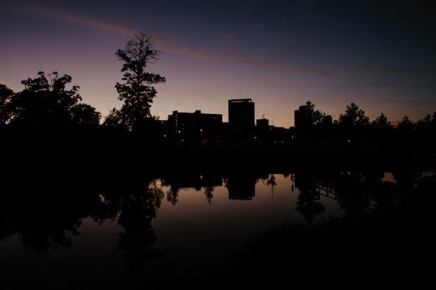 日の出時の建物の湖の反射がある市内の公園