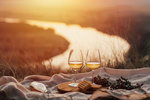 日没時の山でのワインとのパーティー。夏のロマンチックな夜。ピクニック。