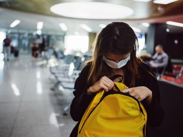 空港の乗客が黄色いバックパックを覗いている女性