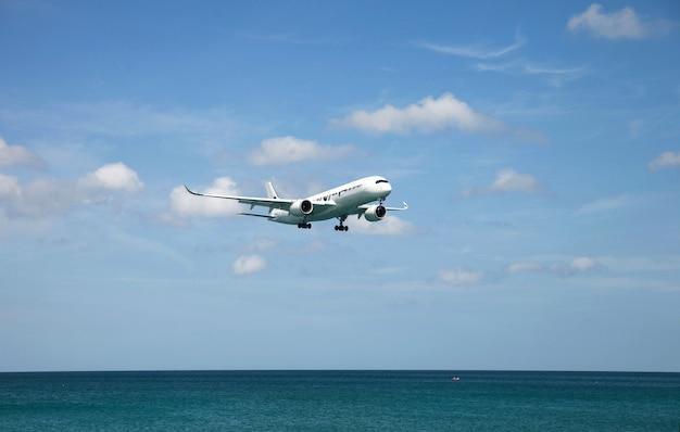 여객기는 여름 휴가 여행에 사용되는 화창한 날 바다 위로 날아갑니다.
