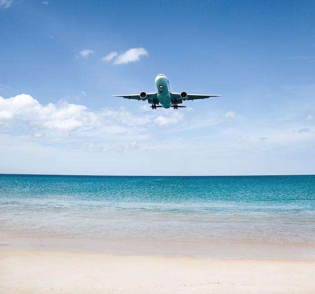 여름 홀 여행에 사용되는 화창한 날에 여객기가 바다 위의 공항에 착륙합니다.