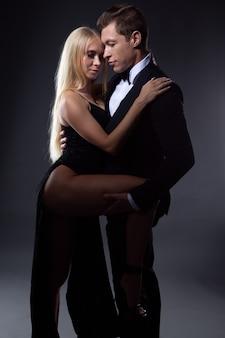 열정적 인 커플 검은 이브닝 드레스에 가벼운 헤어 스타일을 가진 여자와 나비 넥타이와 양복을 입은 잘 생긴 남자