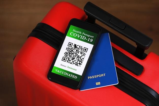 Паспорт и смартфон со справкой о вакцинации от болезни covid-19. сосредоточиться на смартфоне