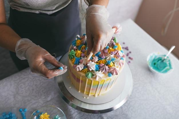 생과자 요리사가 자신의 손으로 웨딩 케이크를 만들고 크림으로 케이크에 화려한 장식을 씁니다.