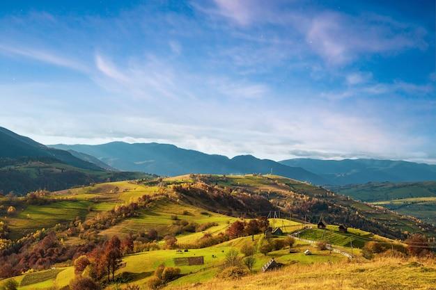 Дорожка по гребню холма с большой лужей и старым забором на фоне леса и неба.