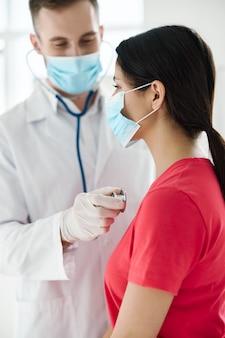 목에 의료 마스크, 보호 장갑 및 청진기를 착용하고 의사가 검사하는 환자