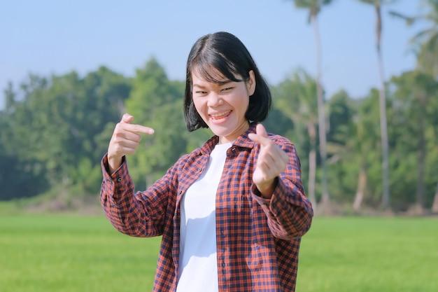 縞模様のシャツを着た農民の女性が喜びのポーズをとり、畑で物を拾っています。顔画像でフォーカスを選択します。