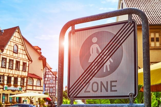 暑い晴れた日に青空とヨーロッパの旧市街に対する歩行者ゾーンの終了サイン。都市環境でのきちんとした安全運転の概念。閉じる。彩色。