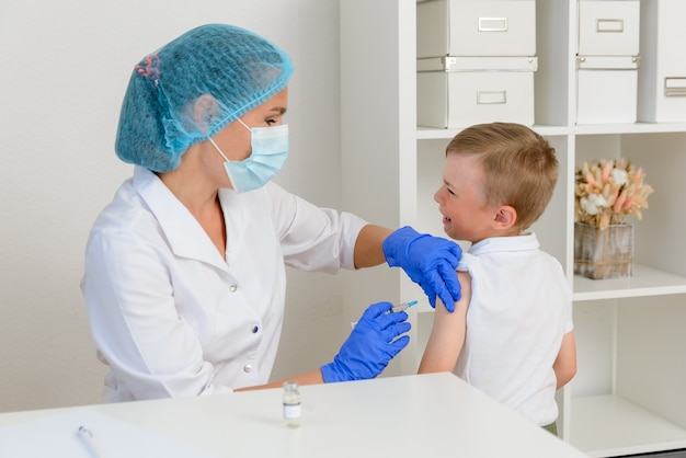 소아과 의사 또는 간호사는 주사로 아픈 아이에게 예방 접종을하기 위해 주사기를 들고