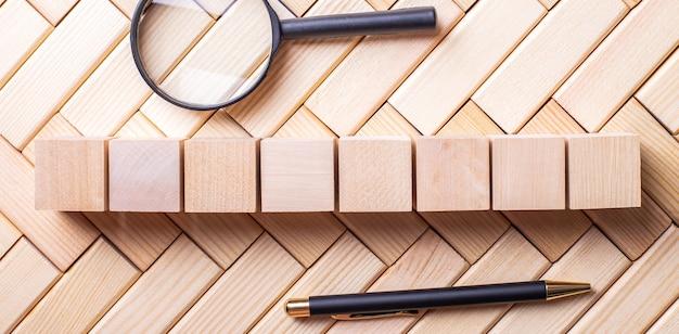 На деревянных блоках лежат ручка, увеличительное стекло и деревянные кубики.