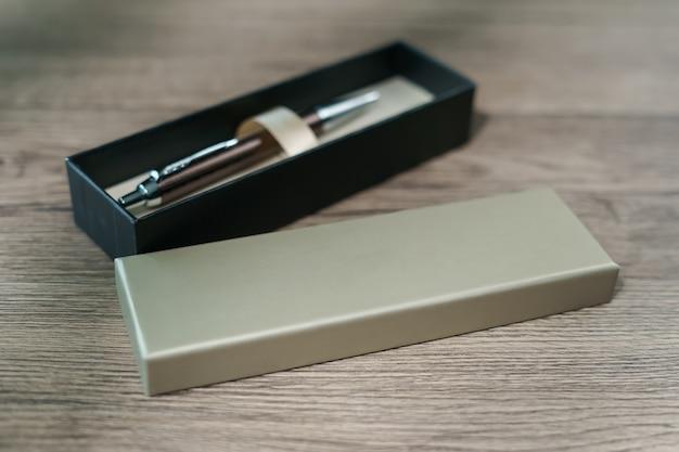 Ручка в подарочной коробке на фоне коричневого дерева стол