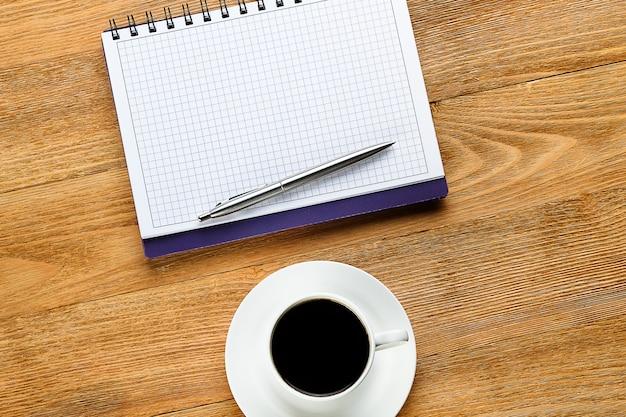 メモ帳のペンと木製のテーブルのコーヒー・マグ。