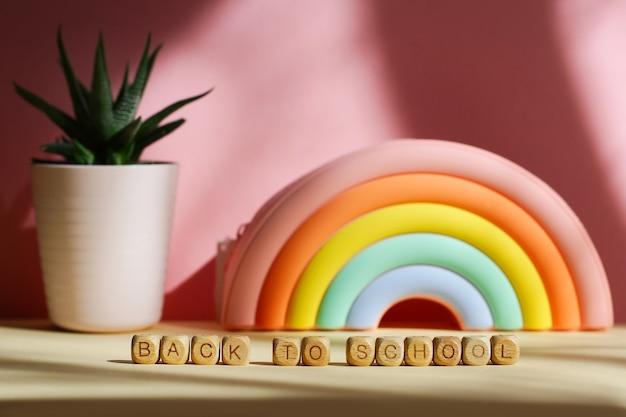 Пенал в виде яркой радуги и суккулента в горшочке на розовом фоне. надпись с деревянными кубиками обратно в школу