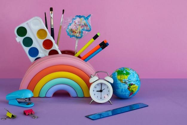Пенал в виде яркой радуги с леденцом в виде единорога, краски, кисти, карандаши, белый будильник, степлер, линейка и игрушечная планета на сиреневом фоне.