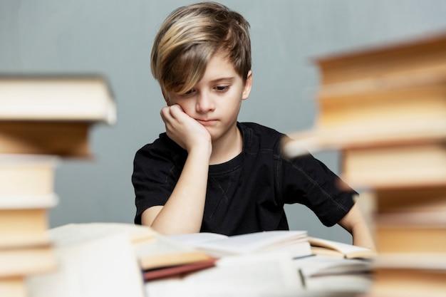9-10세의 생각에 잠긴 소년이 책이 있는 테이블에 앉아 있습니다. 회색 배경입니다. 시험 및 학습 어려움.