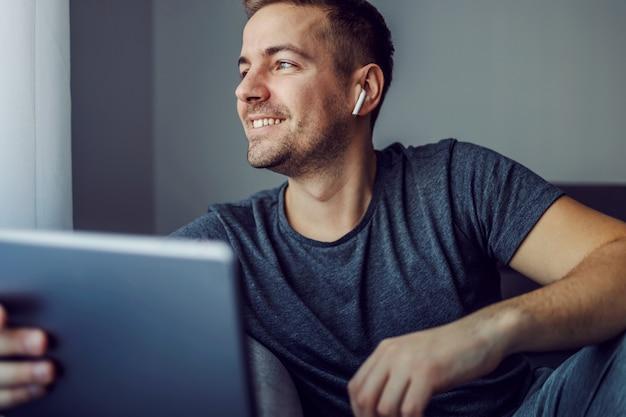Задумчивый мужчина сидит в закрытой комнате и смотрит в окно. слушает музыку в белых беспроводных наушниках. ностальгия в глазах, сохранение социальной дистанции, изоляция