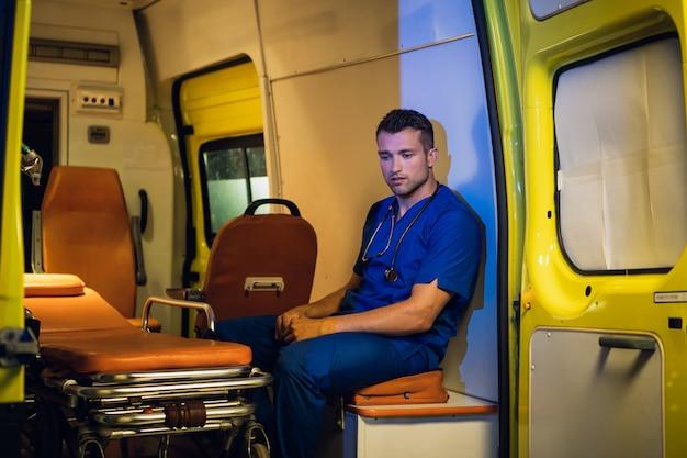 Задумчивый медицинский работник в синей форме сидит в машине скорой помощи и медитирует