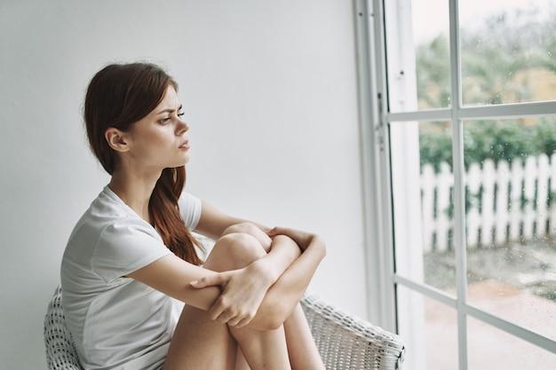 窓の近くの物思いにふける女性が風景に見える