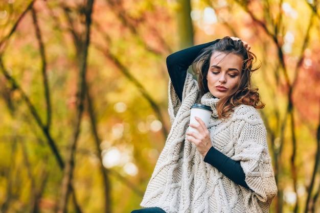 物思いにふける女性が公園で一杯のコーヒーを持って立っています。巻き毛と美しいメイク。秋の公園の背景。閉じる