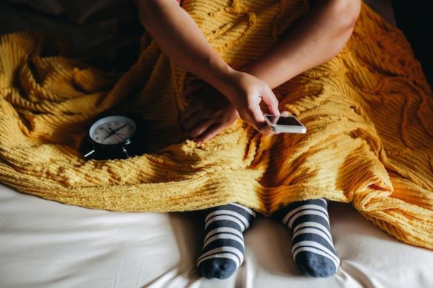 담요 아래 침대에서 양말을 신고 스마트 폰을 사용하는 사람들