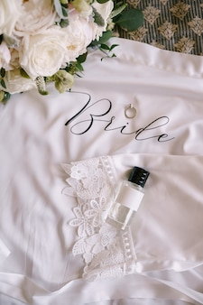 검은 모자가 달린 향수병 돌이 달린 결혼 반지와 흰 장미의 신부 부케