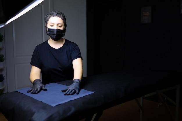 Мастер перманентного макияжа в черной униформе стоит перед диваном в косметологическом кабинете.