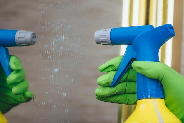 Человек наносит моющее средство на зеркало, используя бутылку с желтой синей крышкой
