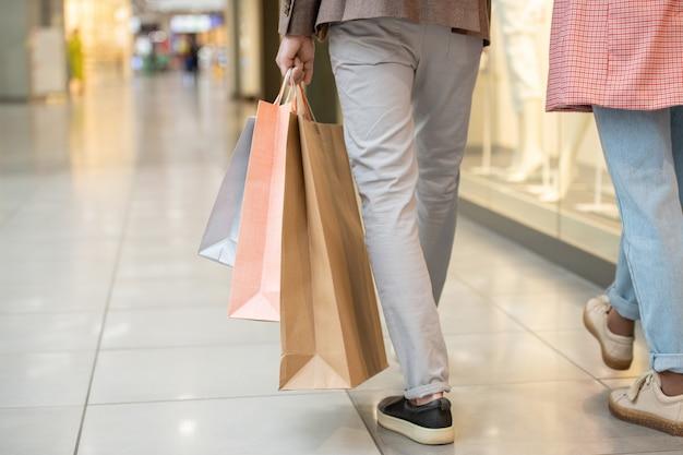 モール内を移動しながら買い物袋を持っている人