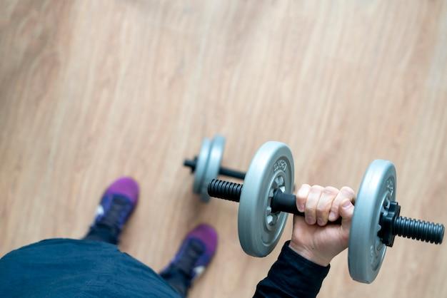 ダンベル器具を使って自宅でトレーニングをしている人
