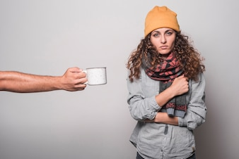 A person giving coffee to sick woman against gray background