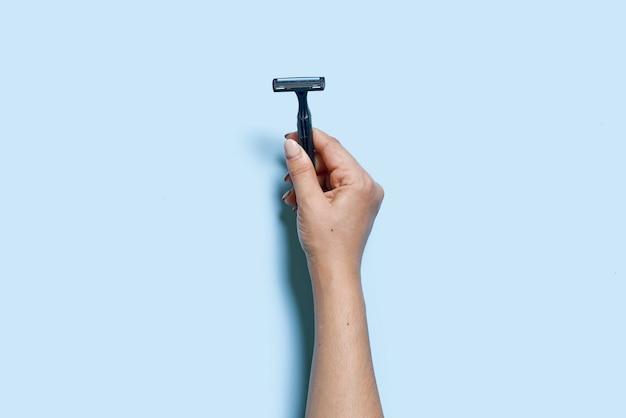 한 사람의 손이 위에서 파란색 배경 보기에 다용도 면도기를 들고 있습니다.