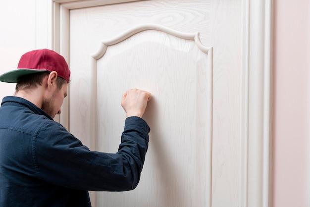 사람 손이 문을 두드리고 친구 집을 방문하십시오.