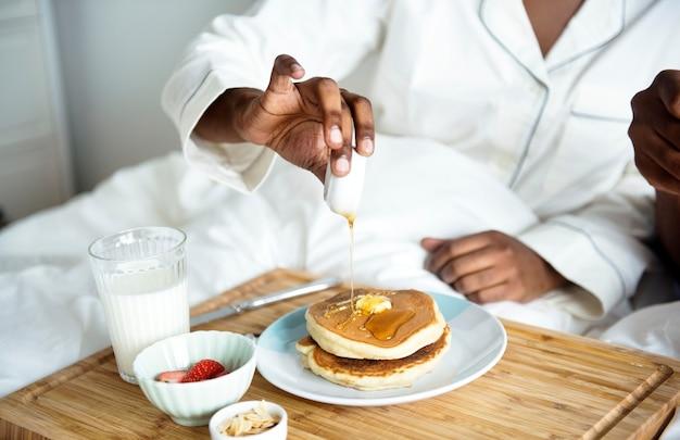 ベッドで朝食をとっている人