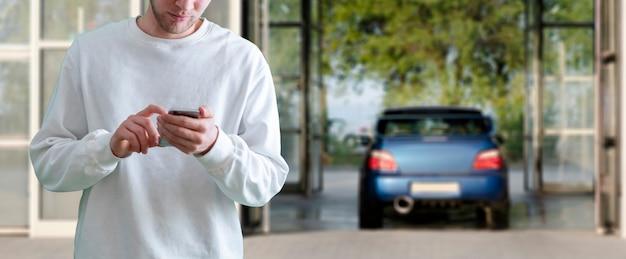 Человек держит смартфон и заряжает аккумулятор электромобиля Premium Фотографии