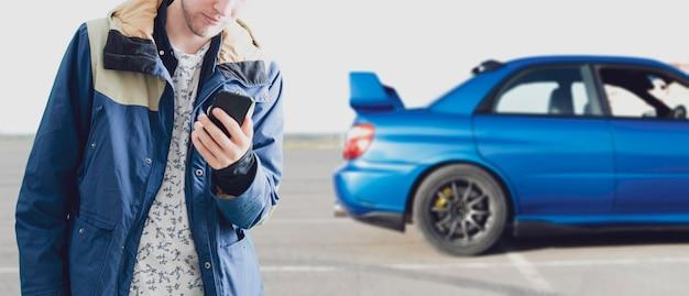 Человек держит смартфон и заряжает аккумулятор электромобиля