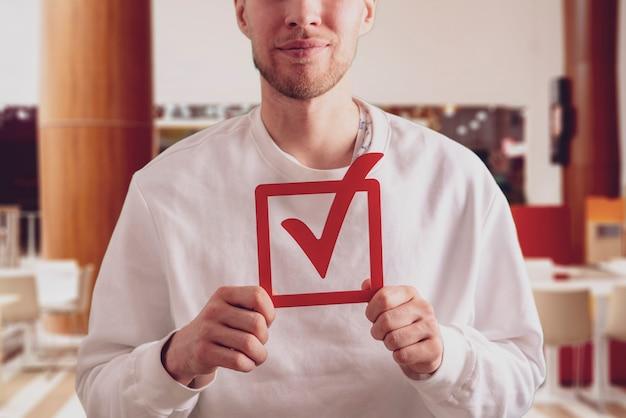 Человек, держащий рамку для голосования, проверяет значок концепции голосования и избирательной демократии в правительстве