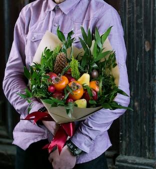 과일 꽃다발을 들고있는 사람