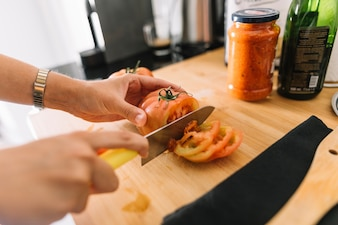 A person holding slices of tomato on chopping board