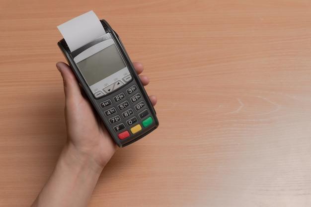 Человек держит в руке терминал для оплаты покупок в магазине банковскими картами или nfc
