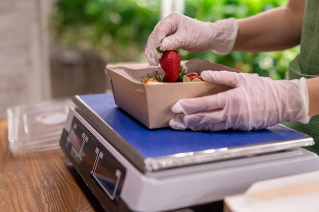 はかりの箱の上にイチゴを持っている手袋をはめた人