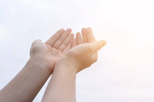 人は、願い事をするように両手を空に向けて、主からの祝福を身振りで示しています。祈りと信仰の概念。新しい人生を共有するという考え。