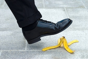 A person is going to step on a banana peel