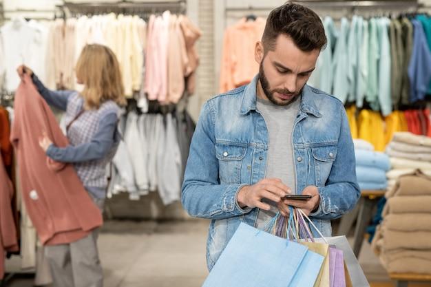 衣料品店で電話を見ている人