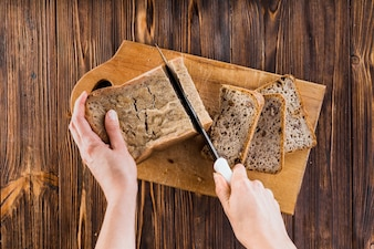 A person making slices of bread with knife on chopping board