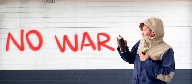 男性がスプレーペイントで書く人は、壁に戦争の声明を止めることができます、落書きのシンボルの概念