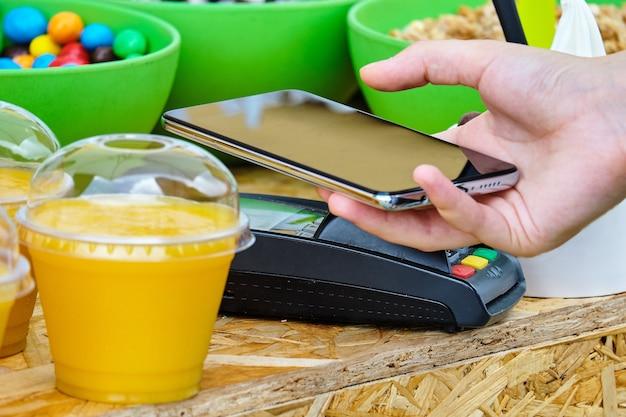 電話で非接触システムnfcを使用して食事代を支払う人