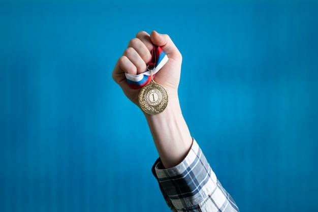 Человек поднял руку, заняв первое место, держит золотую медаль за руку